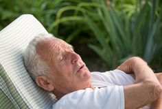 Old man resting in garden stock images