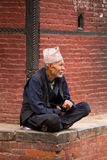 Old man resting and obsertving the street activity in Nepal Royalty Free Stock Photo