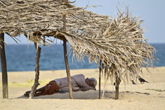 Old man resting in shadow in the beach, Batticaloa, Sri Lanka. An old man is resting under the shadow of a hut in the beach, Batticaloa, Sri Lanka royalty free stock photo