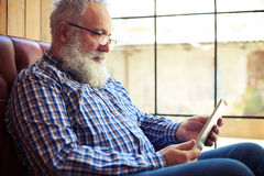 Old man resting on sofa and using tablet pc Royalty Free Stock Photo