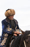 A Old Man rides horse at Song Kul Lake in Kyrgyzstan Stock Photography