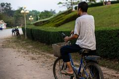 An old man rides an old bike through a park in Laos, Asia. back view royalty free stock image