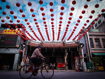 Old Man Riding Bicycle in front of an Asia Temple Royalty Free Stock Image