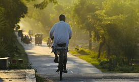 An old man riding a bicycle on a highway road. A man is riding a bicycle on a highway road around an urban area of Bangladesh isolated unique photograph Stock Photo