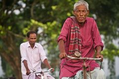 Old man riding a bicycle in a village road unique photo. A Bangladeshi old man riding on a bicycle wearing traditional dress isolated unique photo stock photography