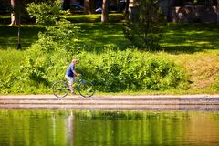 An old man riding a bike near the pond in Park La Fontaine in Montreal Canada royalty free stock images