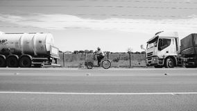 Old man riding a old bicycle selling ice creams on a highway. Campo Grande, Brazil - May 24, 2018: Old man riding a old bicycle selling ice creams on a highway Royalty Free Stock Image