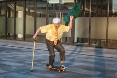 Old man is riding a skateboard. stock photography