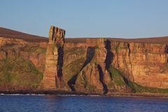 Old Man rock on Orkney Islands. Red sandstone with visible layers on the cliffs of Orkney coast Royalty Free Stock Photography