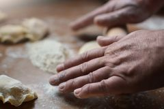 Old man rolls the dough raw hands. Man prepares the dough for the preparation of pasta on a wooden table. Handmade Stock Photography
