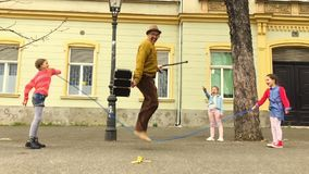Old man rope skipping with three girls. stock footage