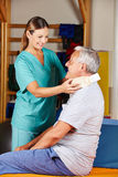 Old man with ruff neck at. Old men with ruff neck and nurse at a physiotherapy Royalty Free Stock Photo