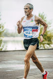 Old man runner running along river. Omsk, Russia -  September 20, 2015: old man runner running along river during Siberian international marathon Royalty Free Stock Photos