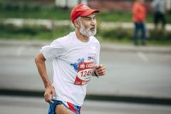 Old man runner running on street city. Omsk, Russia -  September 20, 2015: old man runner running on street city during Siberian international marathon Stock Photos