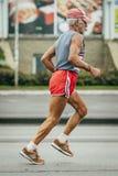 Old man runner running on street. Omsk, Russia -  September 20, 2015: old man runner running on street during Siberian international marathon Stock Image