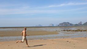 Old man runs along beach at low tide stock video footage