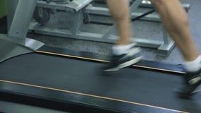 Old man runs on a treadmill stock video