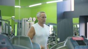 Old man runs on a treadmill stock video footage