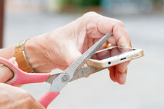 The old man's hand holding scissors and cut mobile phone Royalty Free Stock Photo