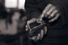 Old man's hands putting coins to a wallet Royalty Free Stock Photos