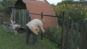 Old man 70s paints the iron fence using a black stock video footage