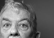 Old man's sad eyes. Black and white. Depression. Close up of an old mans face. Black and white Sad eyes wide open with a haunting expression looking towards the Royalty Free Stock Images