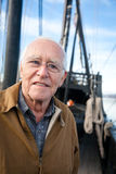 The Old Man Sailor. A close up image of a happy old man standing on the deck an old style wooden sailing ship. There are lots of lines and rigging in the Royalty Free Stock Photography