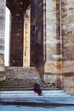 Old man sat on steps of Fleche Saint Michel, Bordeaux. Bordeaux, France - July 22 2018: Old man sat on steps of Fleche Saint Michel, part of Basilique Saint Stock Image