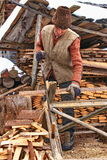 Old man sawing the firewood Stock Photo