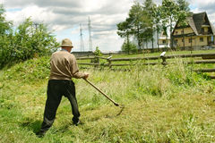 Old man with scythe. Old man mowing down grass with scythe Stock Photo