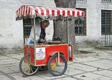 Old man selling baked sweet chestnuts, raw stock image