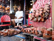 Old man sells a variety of  handcrafted footwear Royalty Free Stock Image