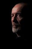 Old man senior in dark. Serious old man senior in light ray on black background Stock Photos