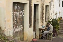 Old man sewing. On a road of Camara de Lobos royalty free stock photography