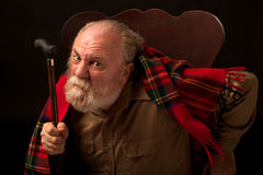 Old man shakes his cane and frowns Royalty Free Stock Images
