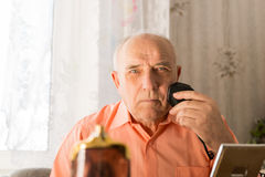 Old Man Shaving Hair on Face with Electric Razor Royalty Free Stock Photography