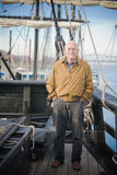 Old Man on a Ship. A happy old man standing on the aft deck an old style sailing ship. The image orientation is vertical and there is copy space Royalty Free Stock Photography