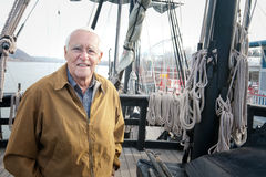 The Old Man and the Ship. A happy old man standing on the aft deck an old style wooden sailing ship. There are lots of lines and rigging in the background. The Stock Photo
