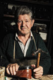 Old man, shoemaker. Repairing old handmade shoe in his workshop and looking at the camera stock photos