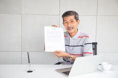 Old man show contract document after sign and smile with happy feeling. In his room office stock photo