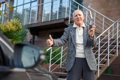 An old man, showing action packed camera and showing a thumbs-up. Outdoors on the street. stock photo