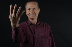 Old man showing four fingers. Senior showing four fingers of his right hand Stock Photo