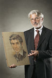 Old man shows his portrait when he was a young man Stock Image