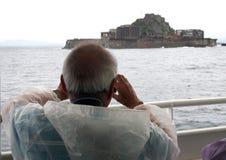 Old man sightseeing near Gunkanjima Hashima or Battleship Island. On board Royalty Free Stock Photography