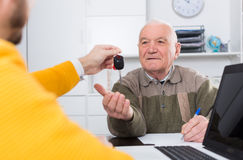 Old man signed car purchase contract. Elderly men and young manager sign car purchase contract and hand over keys royalty free stock image