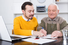 Old man signed car purchase contract. Old men and manager signed car purchase contract at office royalty free stock photos