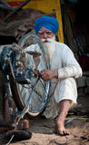 Old man Sikh is repairing the cycle stock photography