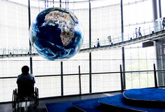 The old man sit in wheelchair for seeing graphic globe. 1 Stock Photography