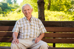 Old man sits on bench. Stock Photography