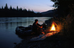 The Old Man Sits On The River Bank By The Fire Stock Photography